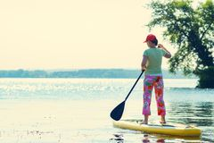 Adult woman is floating on a SUP board on sunny morning. Stand up paddle boarding - awesome active recreation during vacation. Back view royalty free stock images