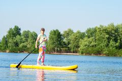 Adult woman is floating on a SUP board. On sunny morning. Stand up paddle boarding - awesome active recreation during vacation stock image