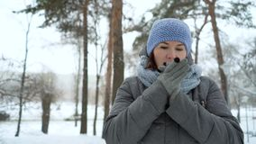 Adult woman freezing on snowy day in winter. Caucasian female breathing on her hands to keep them warm. people, health and comfort stock video