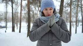 Adult woman freezing on snowy day in winter. Caucasian female rubbing her hands to keep them warm. people, health and comfort stock video footage