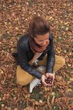 Adult woman gather wild chestnuts from autumn fall leaves. Adult woman gather wild chestnuts from autumn leaves stock images