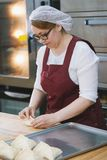 Adult woman in glasses and apron bakes cakes in the bakery half-profile Stock Image