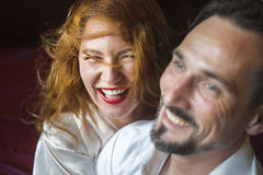 Red hair woman laugh with her man , indoor. Adult women with gold luxuriant hair, painted lips has a great time and laugh together with her men Rasfokus in the Stock Photo
