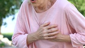 Adult woman having breathing problem, feels heart attack during walk in park. Stock photo royalty free stock photos