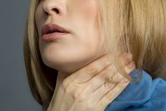 Adult woman having disturbing symptom. Sore throat. Close up of female chin, lady is holding her hand on neck covered with scarf. Isolated on background Royalty Free Stock Photos