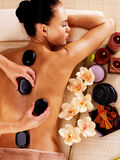 Adult woman having hot stone massage in spa salon. Beauty treatment concept Royalty Free Stock Photography
