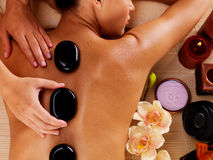 Adult woman having hot stone massage in spa salon Royalty Free Stock Photo