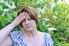 Adult woman with  headache about bird cherry blossoms in spring Royalty Free Stock Photography