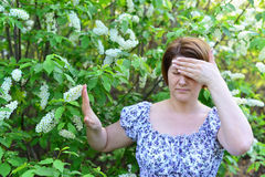 Adult woman with  headache about bird cherry blossoms in spring Stock Photos