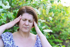 Adult woman with  headache about bird cherry blossoms in spring Stock Images