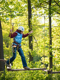 Adult woman in a helmet and with a safety system cautiously walking on suspension bridge on the background of trees Royalty Free Stock Images