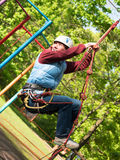Adult woman in a helmet and with a safety system climbs a rope ladder Stock Photos
