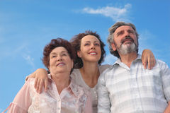 Adult woman and her parents embracing stock images