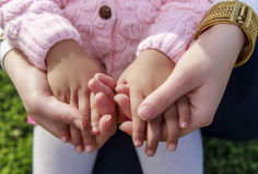 Adult woman hold little girl hands in green garden. Stock Photos