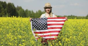 Adult woman holding American flag with pole, stars and stripe in a yellow rapeseed field. USA flag fluttering in the wind stock footage