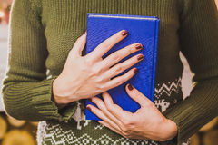 Adult woman holding blue book Royalty Free Stock Photography