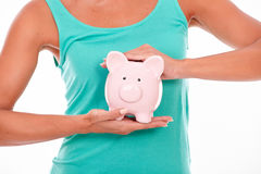 Adult woman holding pink piggy bank. Adult caucasian woman holding pink piggy bank with both hands in front of her wearing a green tank top on a white background Stock Photo