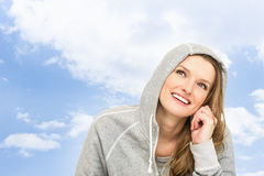 Adult woman with a hood and the sky. Smiling. Portrait of adult woman in a sport coat with a hood against the winter sky. Smiling girl and closeup . She is Stock Photos