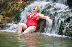 Adult Woman In Red Swimsuit Enjoying A Waterfall Royalty Free Stock Photos