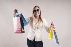 Adult woman surprise in a jacket  packages emotion american  housewife purchases in  studio. Adult woman in a jacket with packages for purchases in   discount Stock Photos