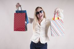 Adult woman surprise in a jacket with packages emotion american  housewife purchases in  studio. Adult woman in a jacket with packages for purchases in  studio Royalty Free Stock Photos