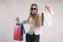 Adult woman in a jacket with packages for purchases in sunglasses studio. Discount Stock Photo