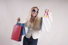 Adult woman surprise in a jacket with packages for purchases in sunglasses studio. Adult woman in a jacket with packages for purchases in sunglasses studio Royalty Free Stock Photo