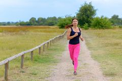 Adult woman jogging towards camera along road. Adult woman wearing black shirt and pink pants jogging towards camera along dirty road with trees in background royalty free stock images