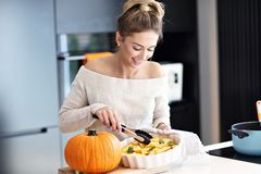 Adult woman in the kitchen preparing pumpkin dishes for Halloween Stock Photography