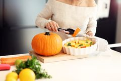 Adult woman in the kitchen preparing pumpkin dishes for Halloween Royalty Free Stock Photos