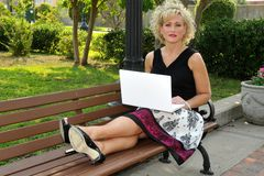 Adult woman on a laptop in a park Stock Image
