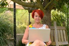 Adult Woman with Laptop Sitting Under the Tree Stock Photo