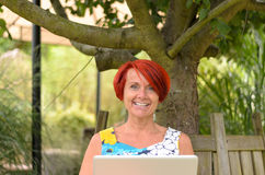 Adult Woman with Laptop Sitting Under the Tree Stock Photos