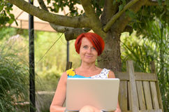 Adult Woman with Laptop Sitting Under the Tree Stock Image
