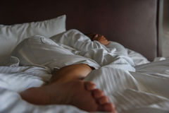 Adult woman laying in bed in morning light covering face. Depressed woman laying in bed in daylight stock photo