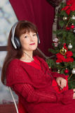 Adult woman listening music against Christmas tree Stock Photography