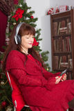 Adult woman listening music against Christmas tree Royalty Free Stock Photography