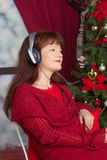 Adult woman listening music against Christmas tree Stock Photo