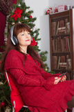 Adult woman listening music against Christmas tree Royalty Free Stock Photo