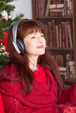 Adult woman listening music against Christmas tree Stock Images