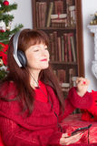 Adult woman listening music against Christmas tree Royalty Free Stock Images