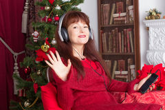 Adult woman listening music against Christmas tree Royalty Free Stock Image