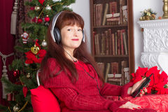 Adult woman listening music against Christmas tree Stock Photos
