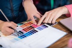 Adult woman and a little girl are choosing a color for clothing together. royalty free stock images