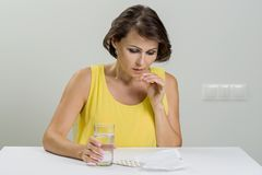 Adult woman looking at instructions, holding a package of pills. Royalty Free Stock Photography