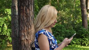 Adult woman looking in mobile phone while walking in green park at summer day. Beautiful woman using mobile phone in summer park at sunny day stock video