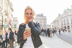 Adult woman looking at smart phone in London Stock Image