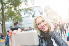 Adult woman looking at smart phone in London Royalty Free Stock Photography