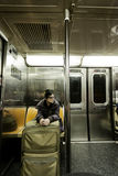 Woman with Suitcase in New-York Subway. An adult woman with luggage sitting in the Brookly bound (downtown) A train subway in Manhattan Royalty Free Stock Photos