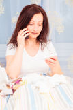 Adult Woman Lying Sick In Bed. Talking on the phone to her medic Stock Photography